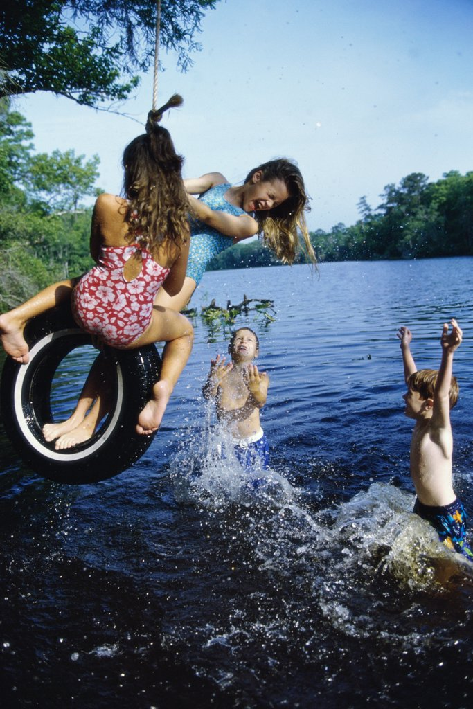 Group of children playing on a tire swing : Stock Photo