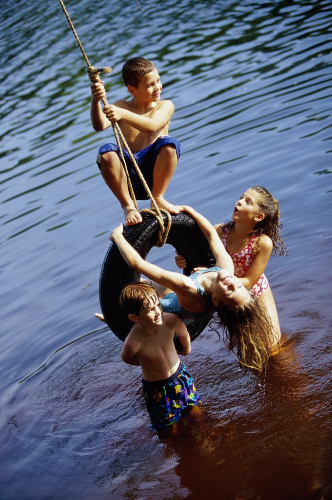 Stock Photo: 1574R-03094A Group of children playing on a tire swing
