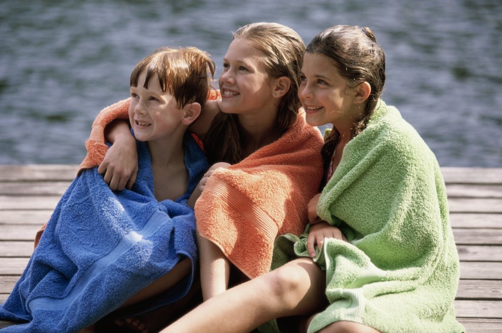 Two girls and a boy wrapped in towels sitting on a dock : Stock Photo