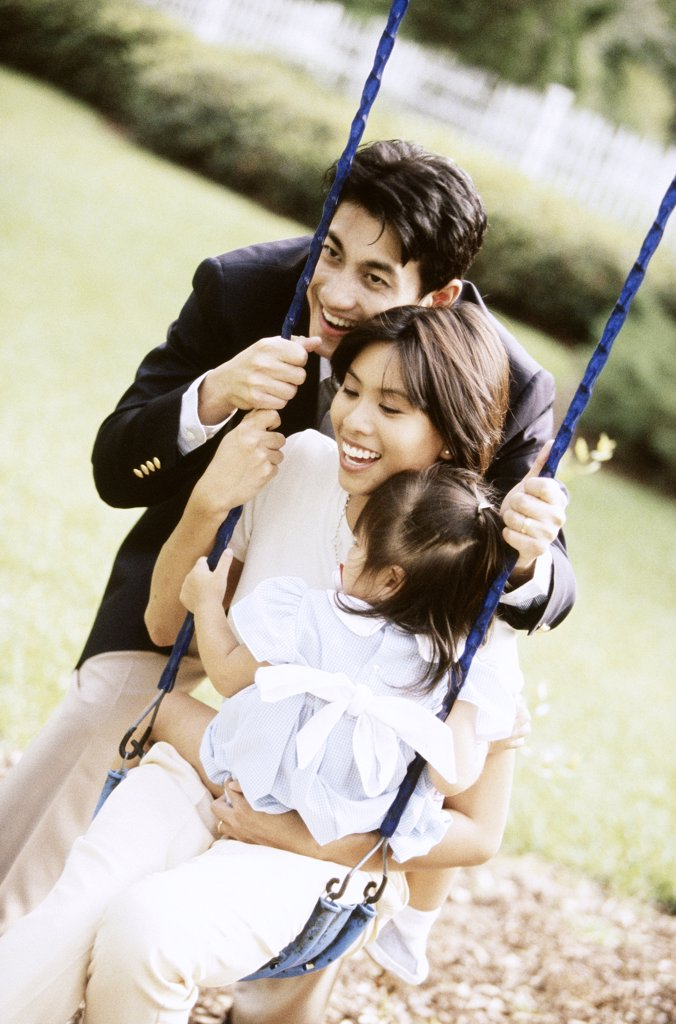 Close-up of parents playing with their daughter on a swing : Stock Photo