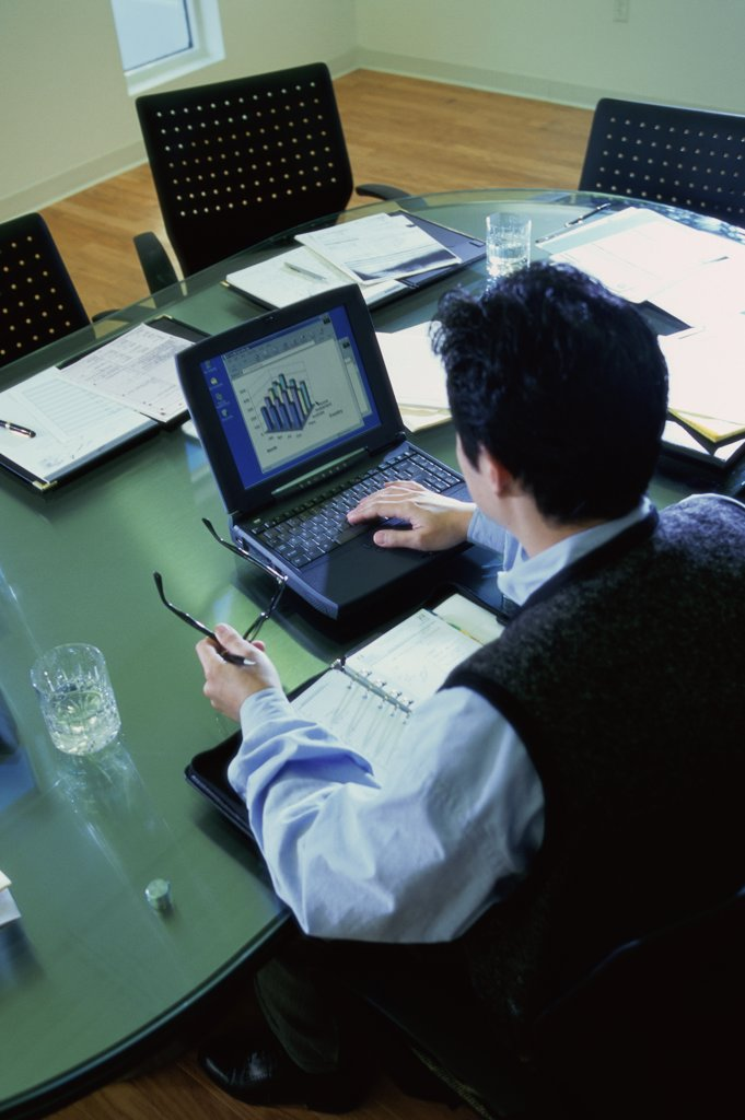 High angle view of a businessman operating a laptop : Stock Photo