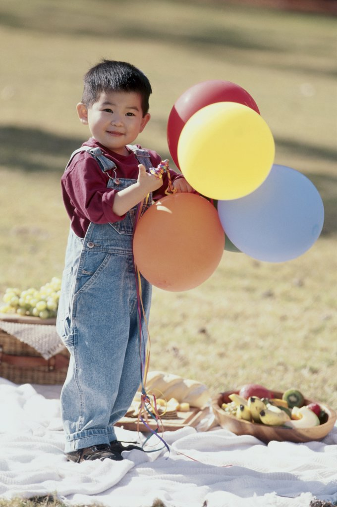Stock Photo: 1574R-03235 Portrait of a boy holding balloons