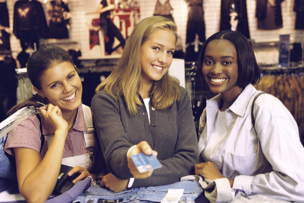 Portrait of three teenage girls at a store counter : Stock Photo