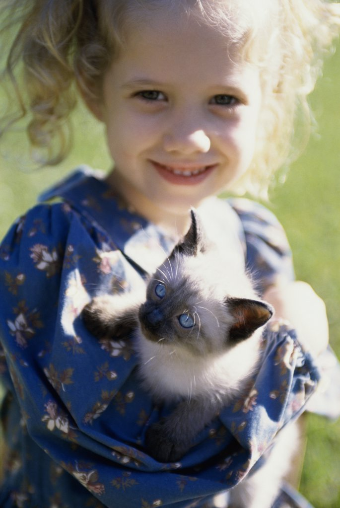 Portrait of a girl holding a Siamese kitten : Stock Photo