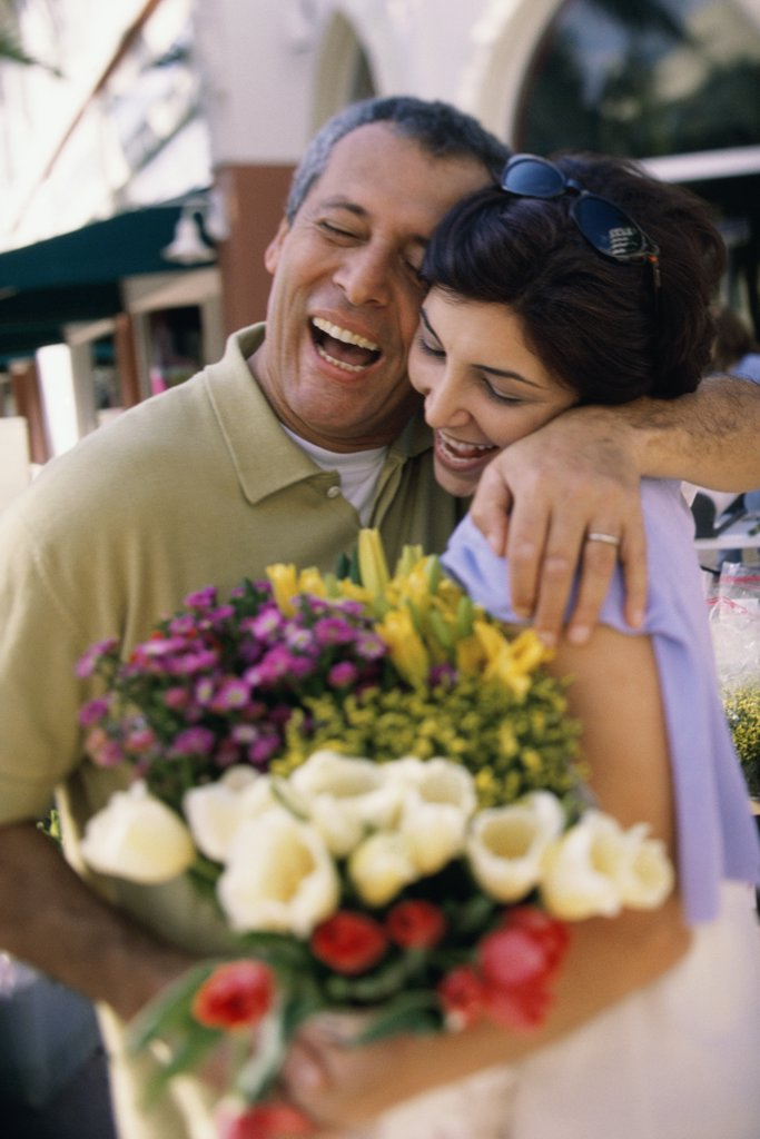 Couple smiling holding a bouquet of flowers : Stock Photo