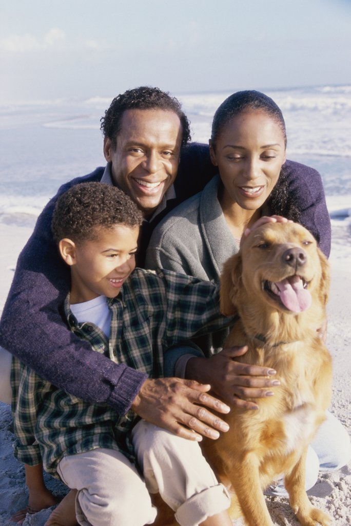 Parents with their son holding a dog : Stock Photo