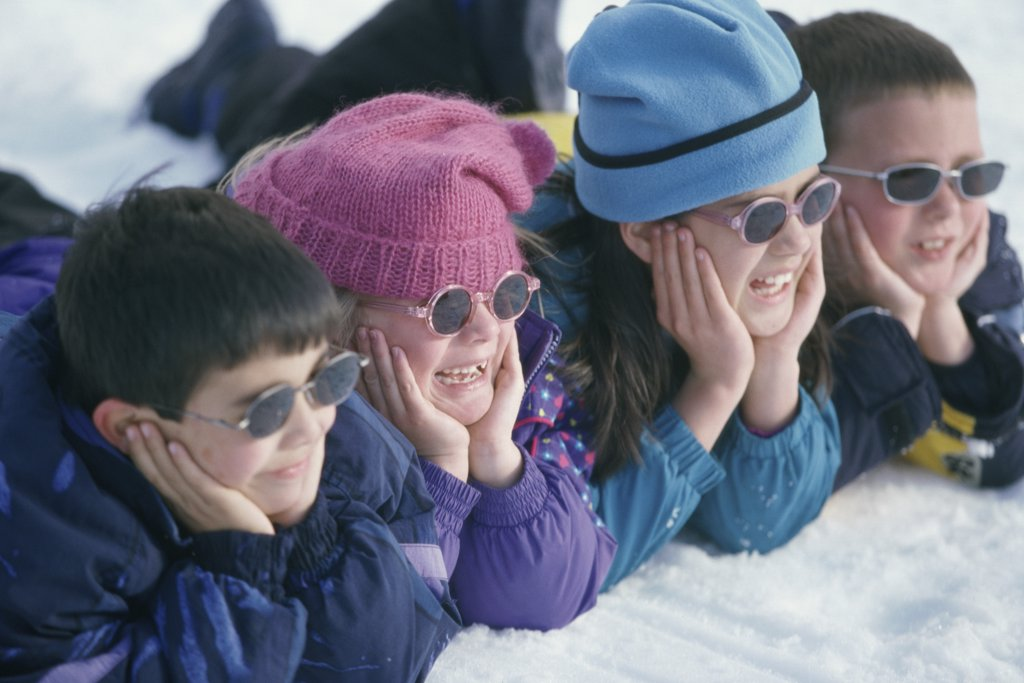 Close-up of a group of children lying in snow : Stock Photo