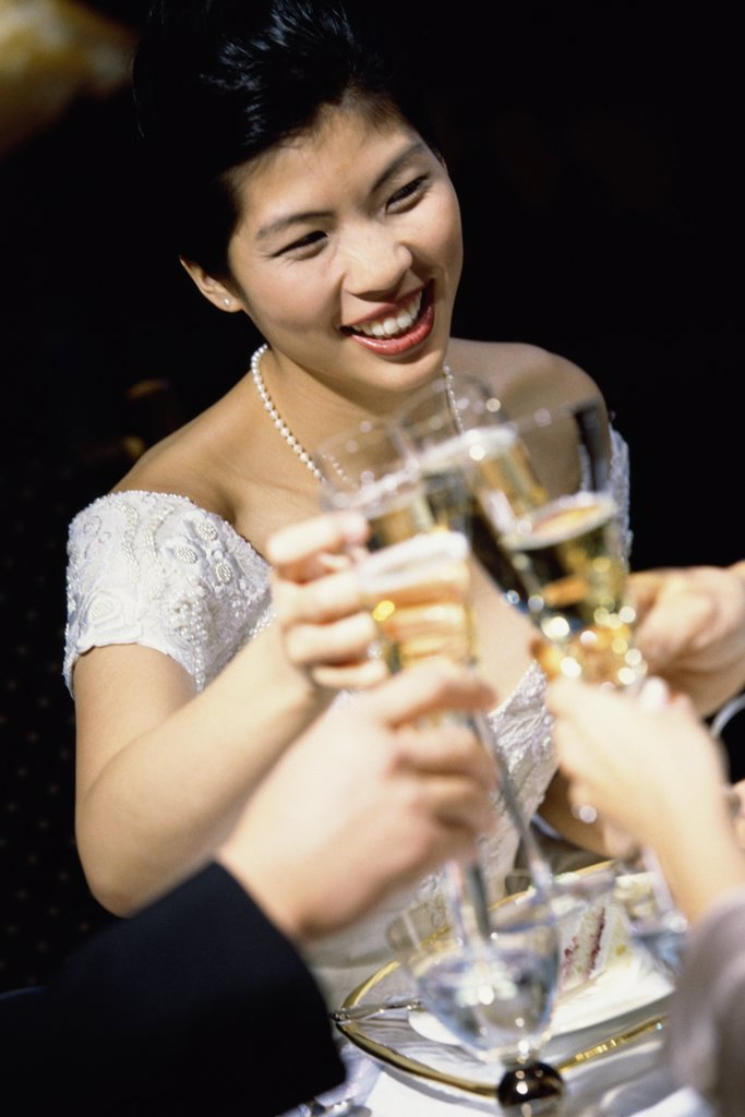 Stock Photo: 1574R-03757 Bride toasting with glasses of champagne