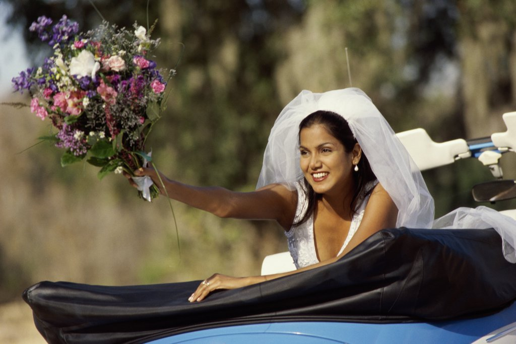 Stock Photo: 1574R-03793 Bride preparing to toss a bouquet of flowers from a convertible car