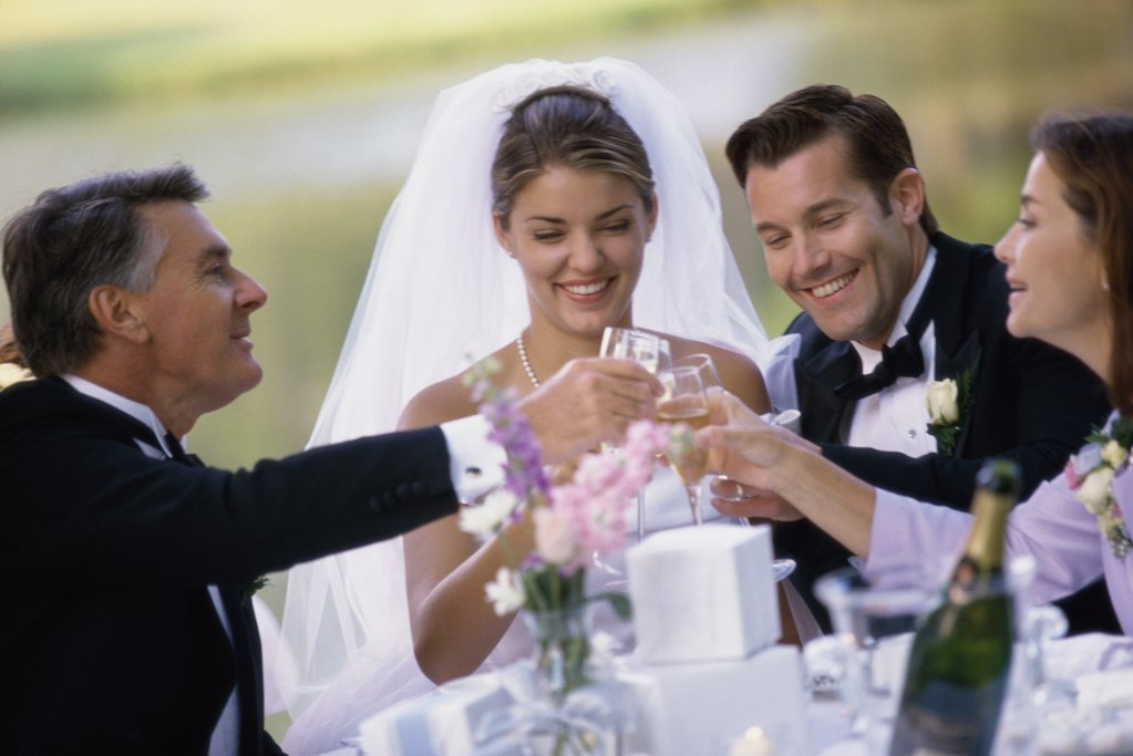 Newlywed couple toasting with their parents : Stock Photo