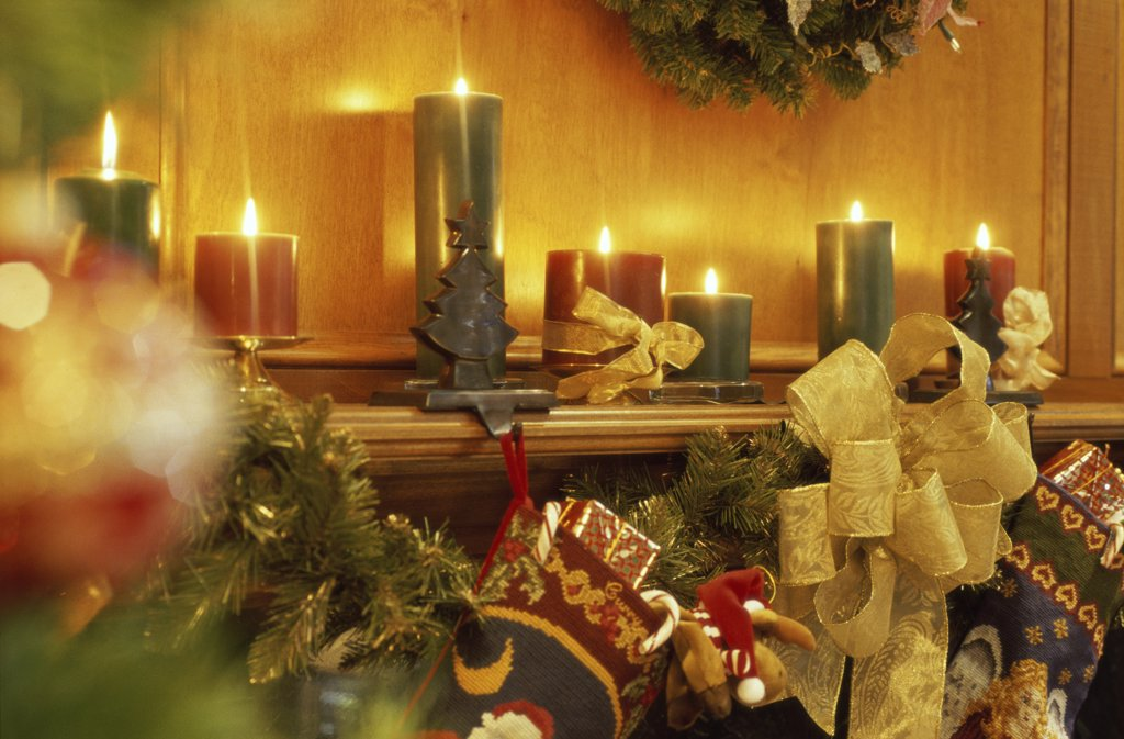 Stock Photo: 1574R-03940 Lit candles and Christmas decorations on a mantelpiece