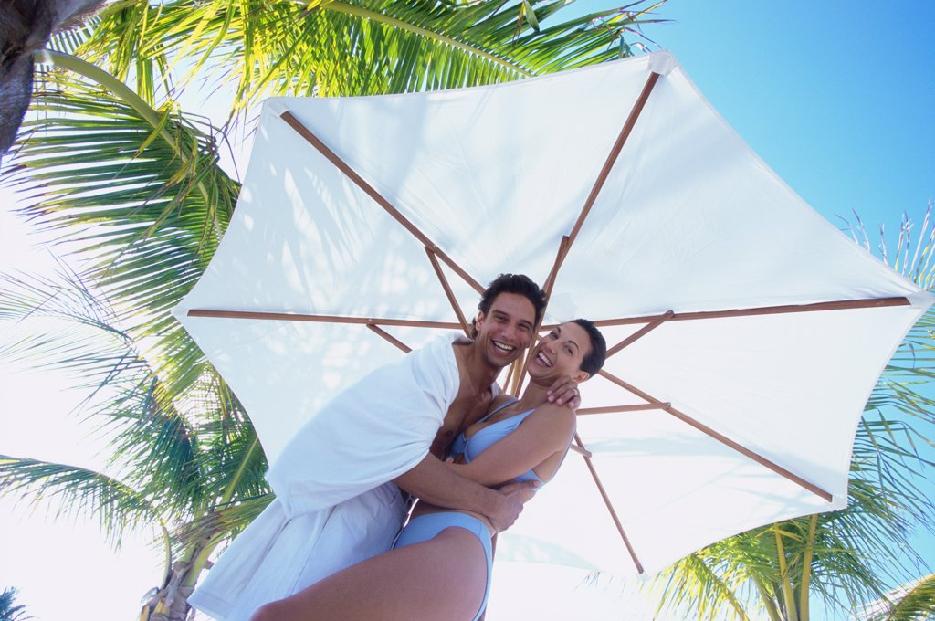 Portrait of a young couple holding each other under a beach umbrella : Stock Photo