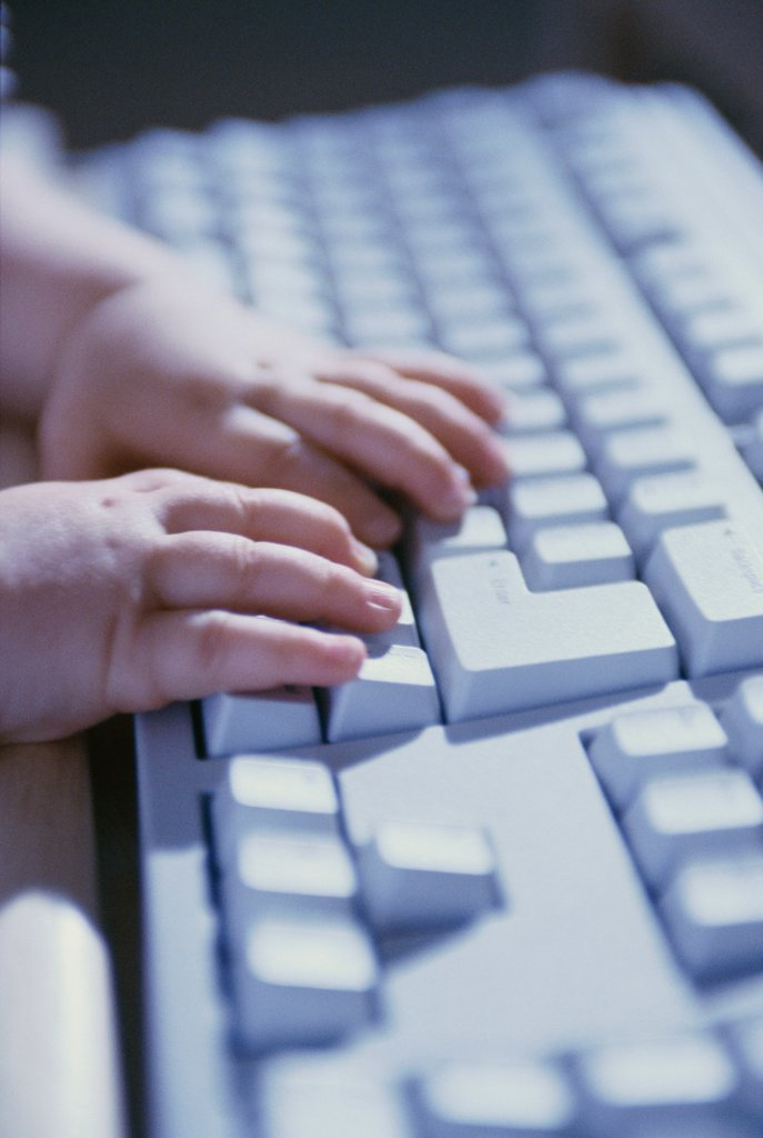 Close-up of a baby's hands on a computer keyboard : Stock Photo