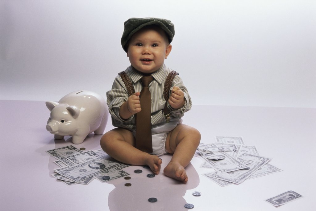 Stock Photo: 1574R-04114 Portrait of a baby boy sitting on the floor with a piggy bank and money