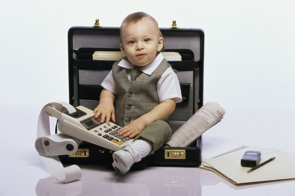 Portrait of a baby boy sitting in an open briefcase holding an adding machine : Stock Photo
