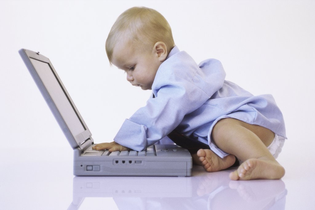 Side profile of a baby boy touching a laptop : Stock Photo