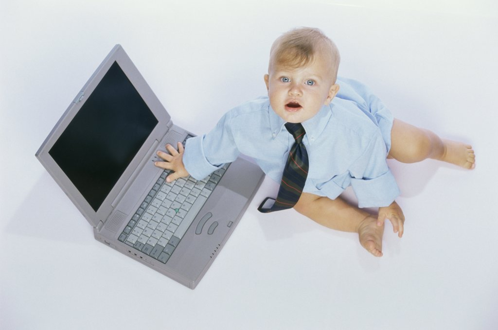 Portrait of a baby boy touching a laptop : Stock Photo