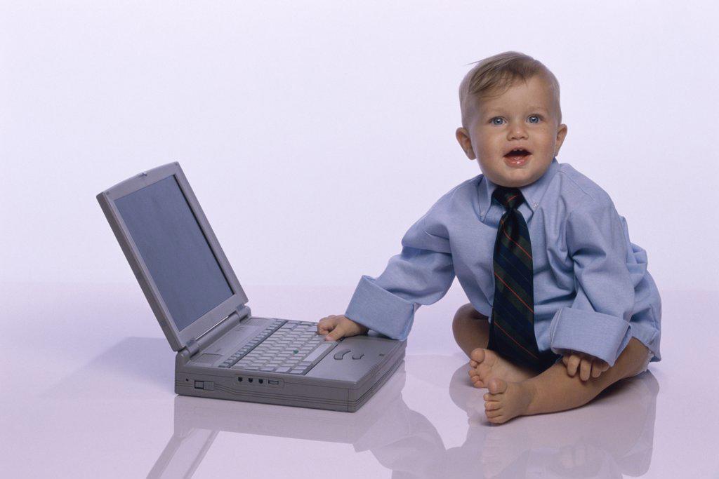 Stock Photo: 1574R-04171 Baby boy touching a laptop