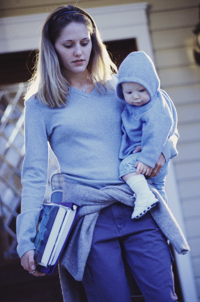 Teenage girl carrying her baby boy and books : Stock Photo