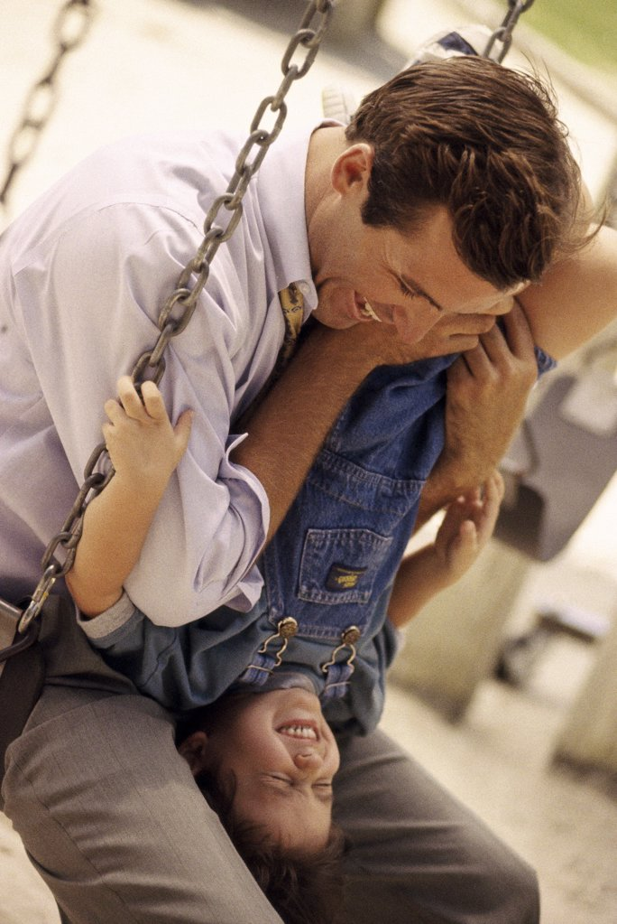 Father sitting on a swing with his daughter : Stock Photo