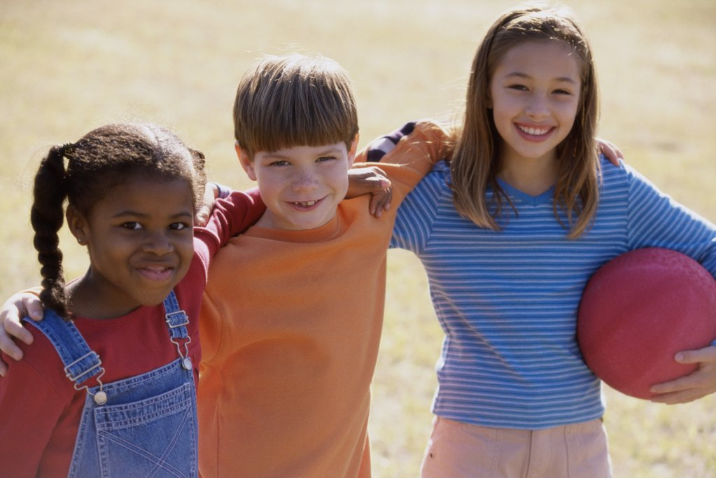 Stock Photo: 1574R-04386 Portrait of girls and a boy standing on a lawn holding a ball