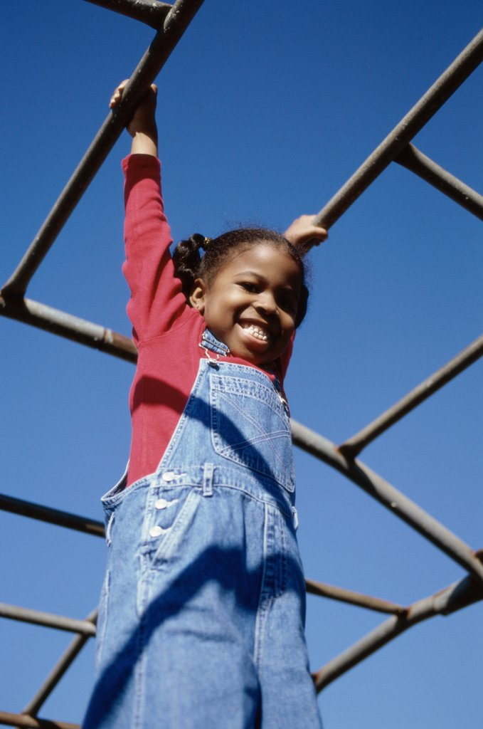Low angle view of a girl hanging on monkey bars : Stock Photo
