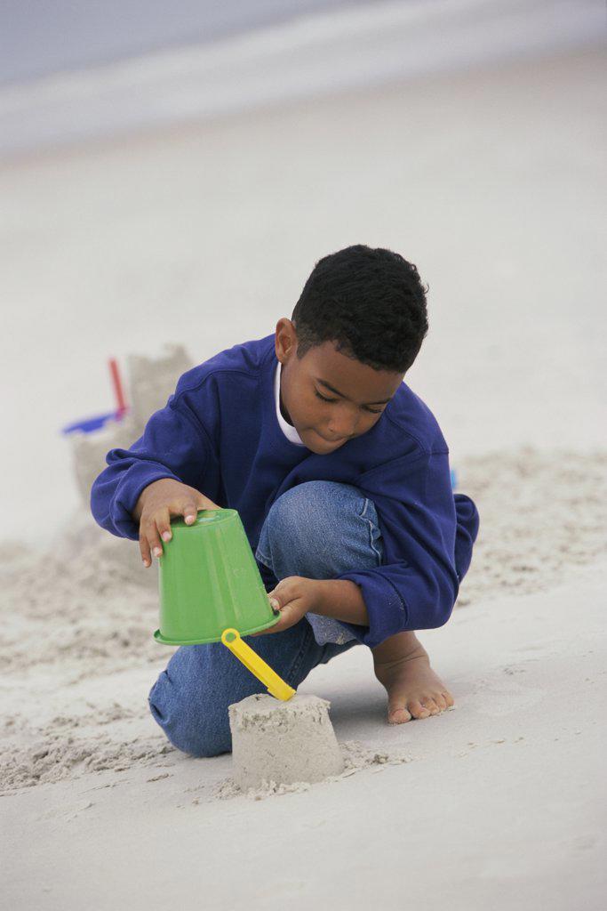 Boy building a sand castle on the beach : Stock Photo