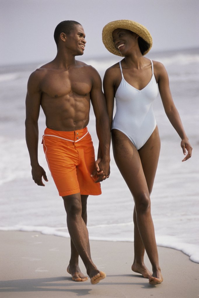 Young couple walking on the beach together : Stock Photo