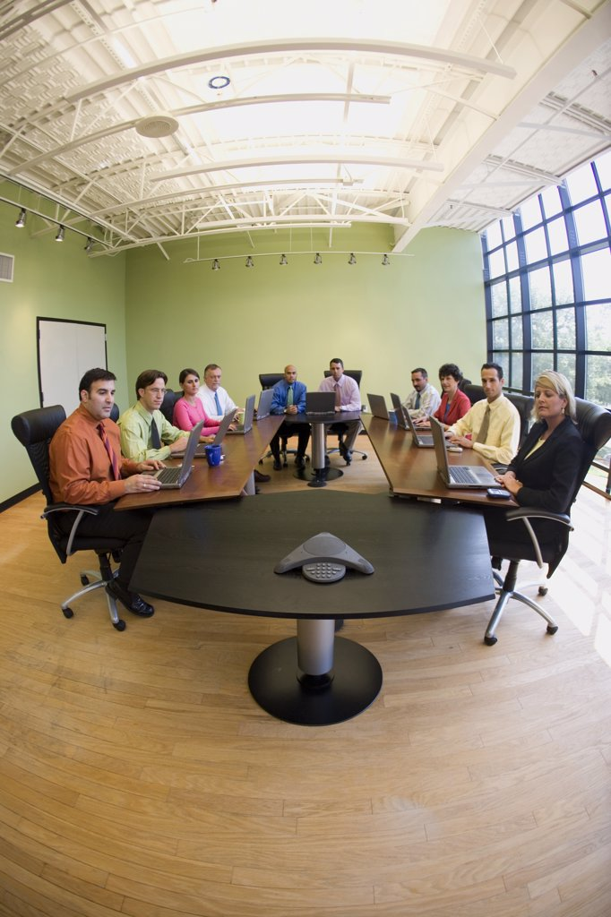 Portrait of a group of business executives sitting in a conference room : Stock Photo