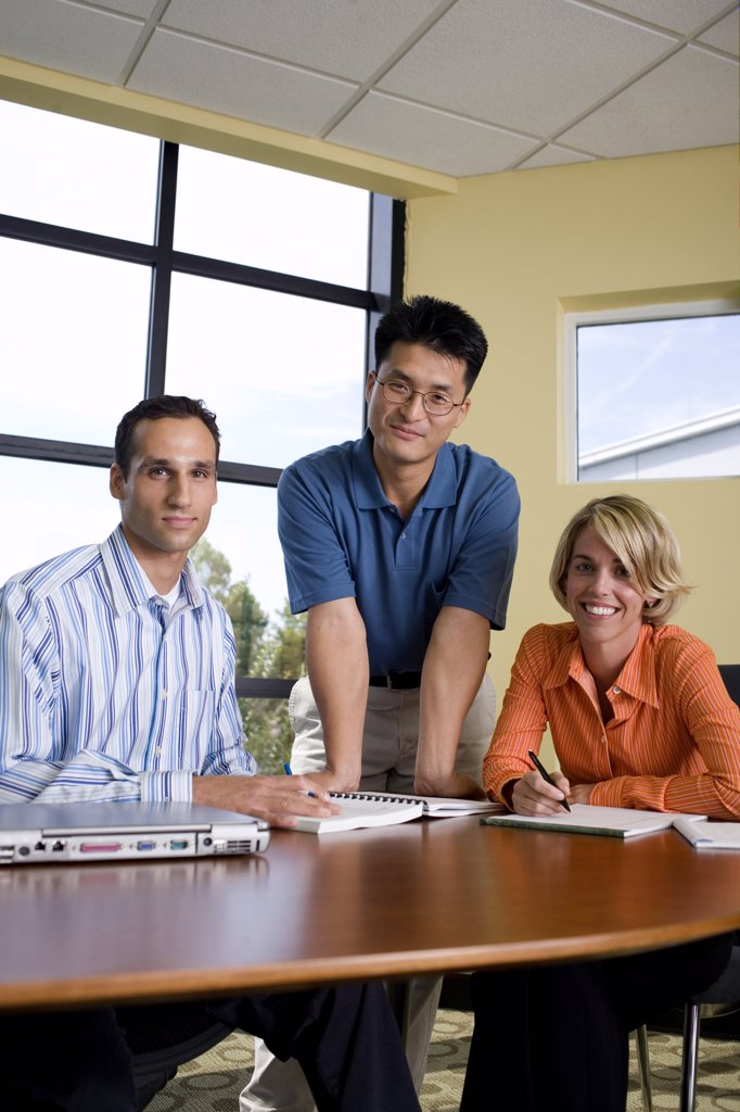 Portrait of two businessmen and a businesswoman in a conference room : Stock Photo