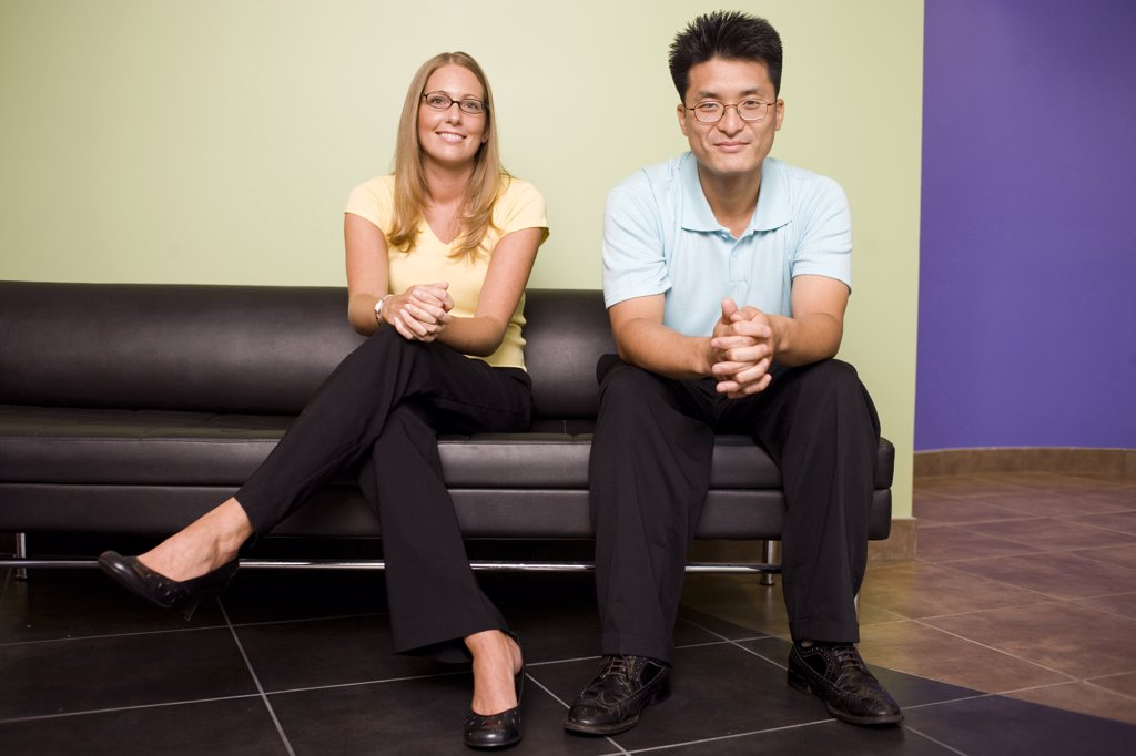 Portrait of a businessman and a businesswoman sitting on a couch in an office : Stock Photo
