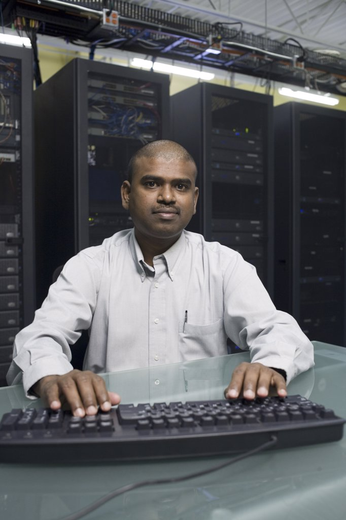 Portrait of a technician working on a network server : Stock Photo