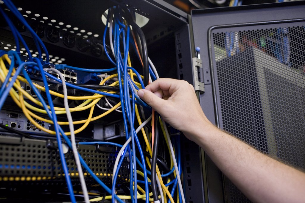 Close-up of a human hand attaching cables to a network server : Stock Photo