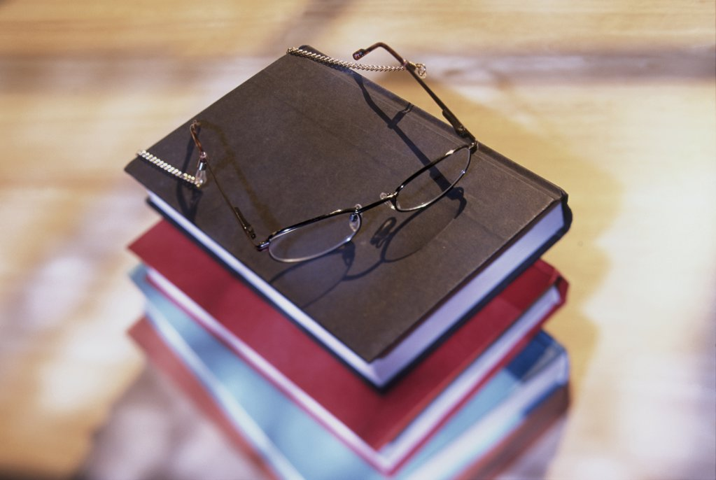 High angle view of stack of books with eyeglasses resting on top : Stock Photo