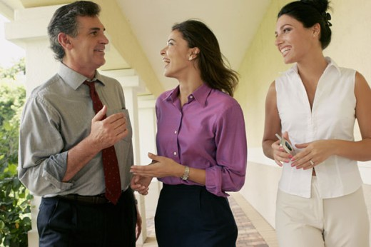 Two businesswomen and a businessman walking in corridor : Stock Photo