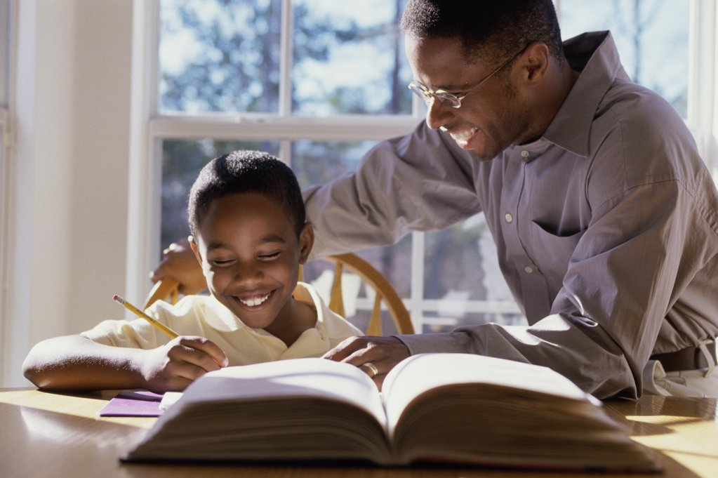 Father helping his son with homework : Stock Photo