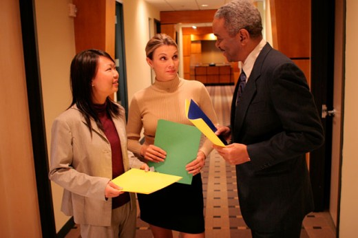 Businessman standing in a corridor talking to two businesswomen : Stock Photo