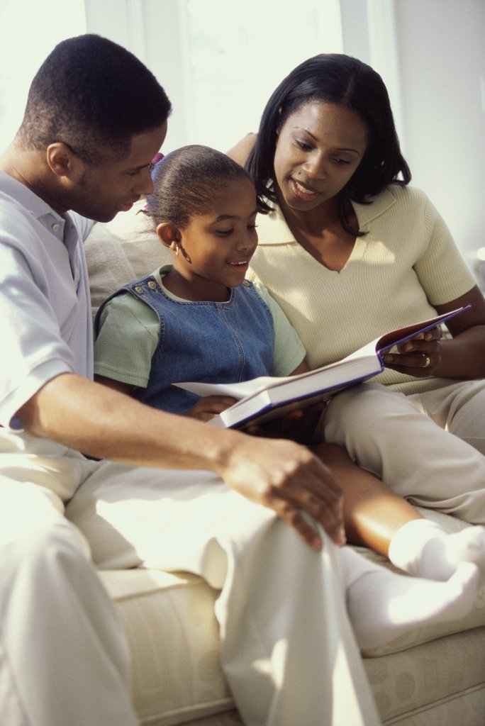 Parents reading a book with their daughter : Stock Photo