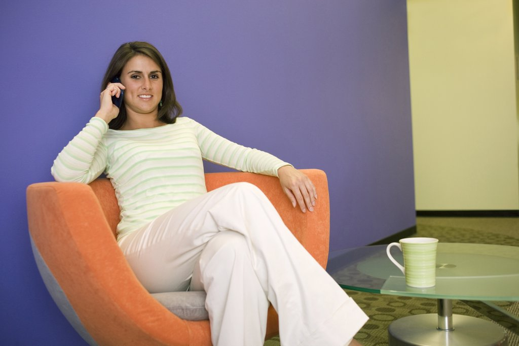 Stock Photo: 1574R-05813 Businesswoman sitting on a chair talking on a mobile phone