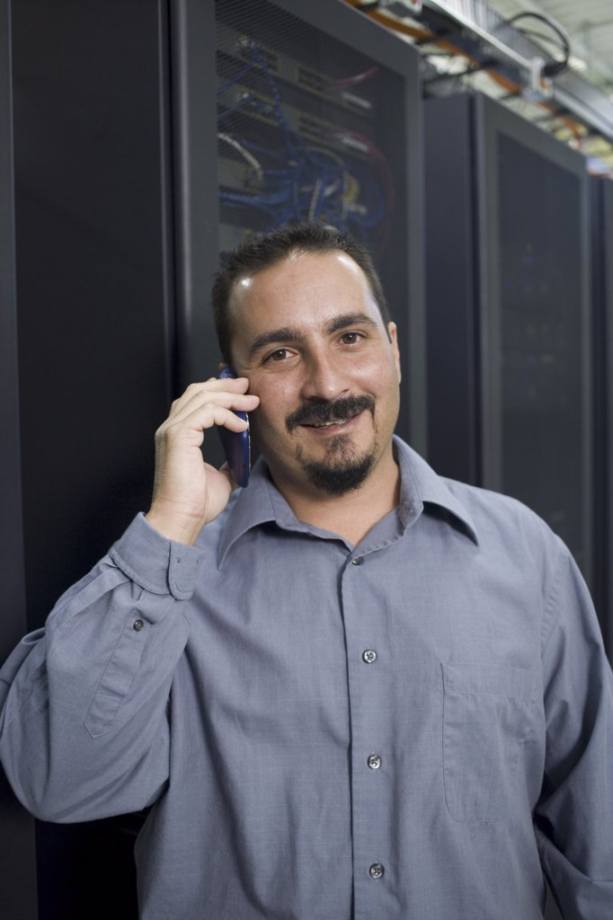 Portrait of a male technician talking on a mobile phone : Stock Photo