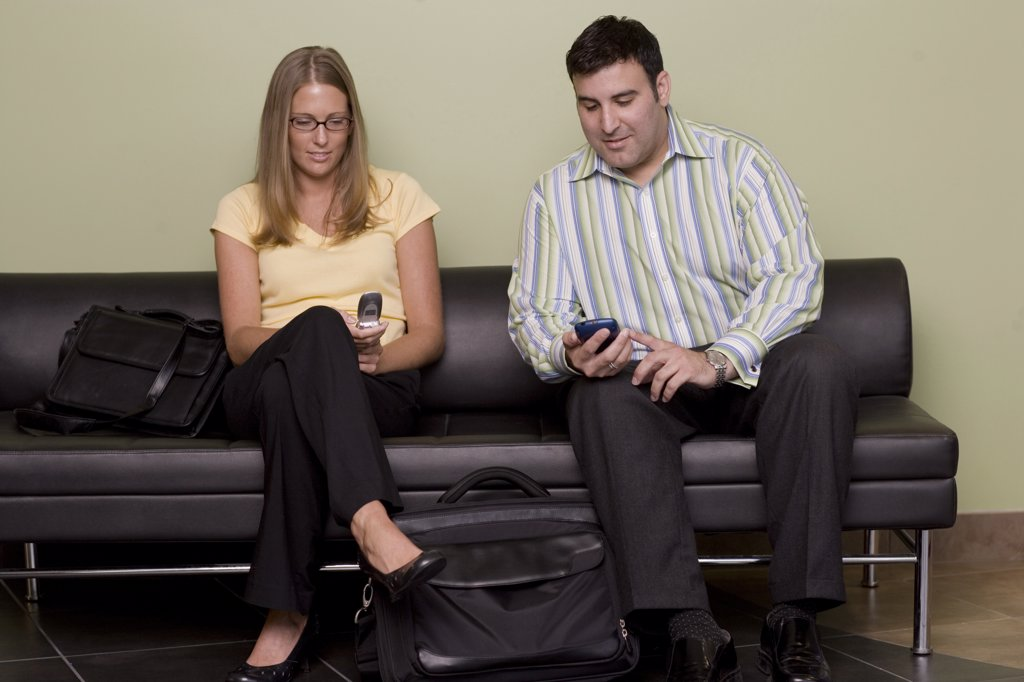 Stock Photo: 1574R-05831 Businessman and a businesswoman sitting on a couch holding mobile phones