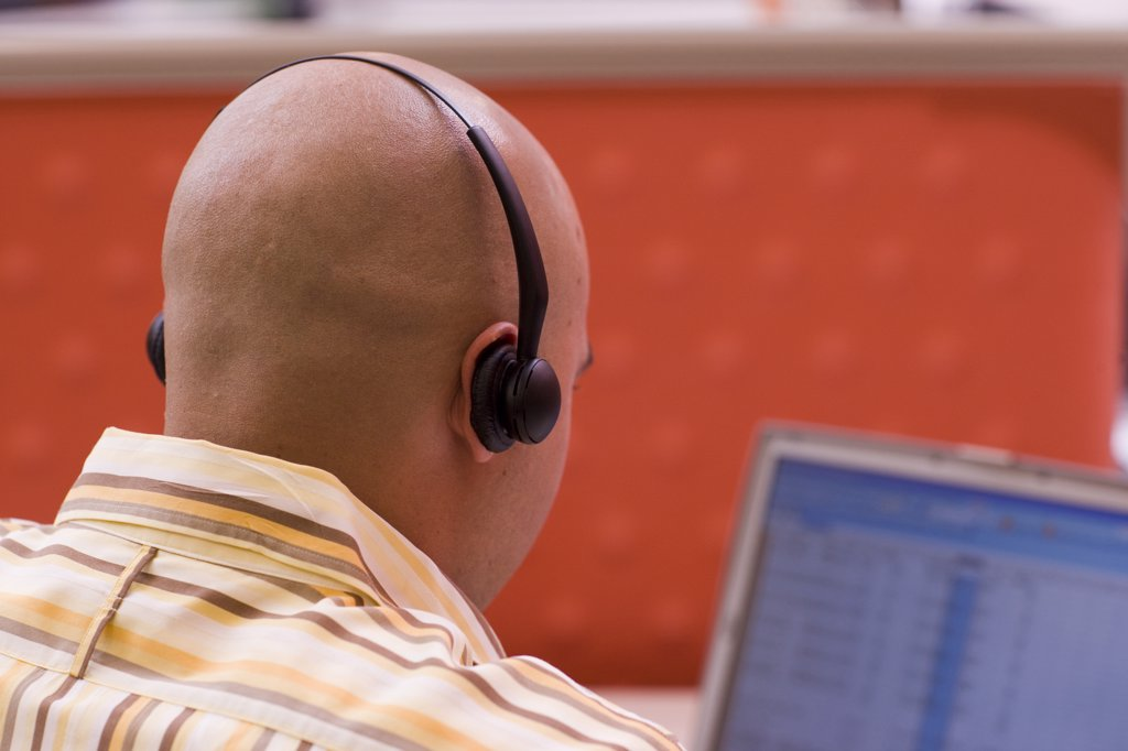 Rear view of a male customer service representative wearing a headset sitting in front of a laptop : Stock Photo