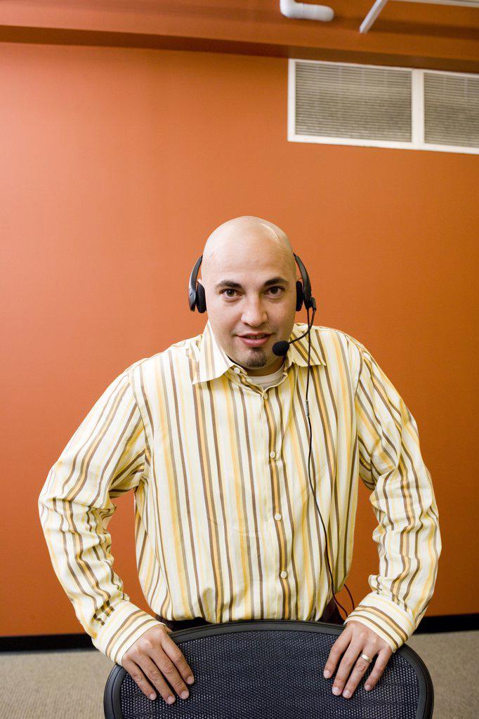 Portrait of a male customer service representative wearing a headset : Stock Photo
