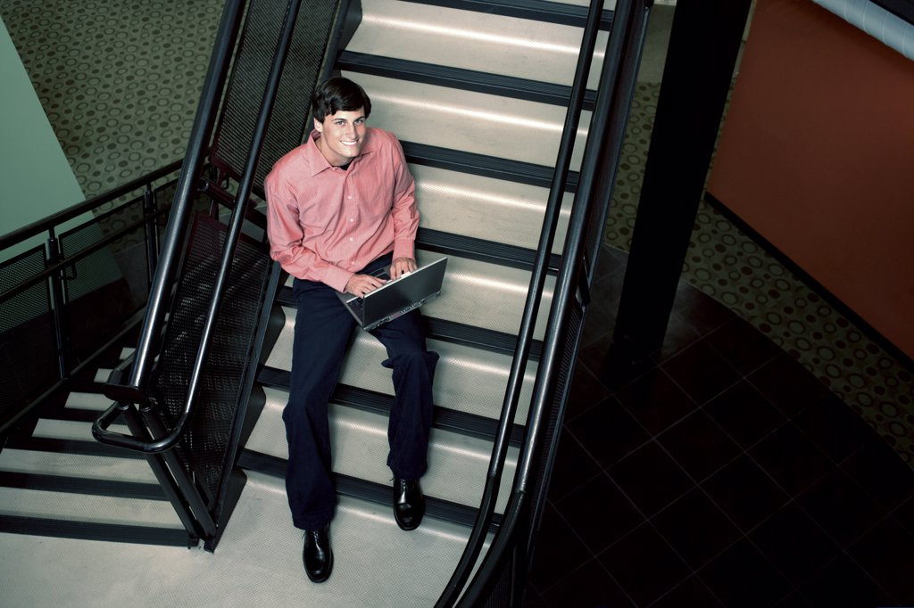 Portrait of a businessman sitting on stairs working on a laptop : Stock Photo