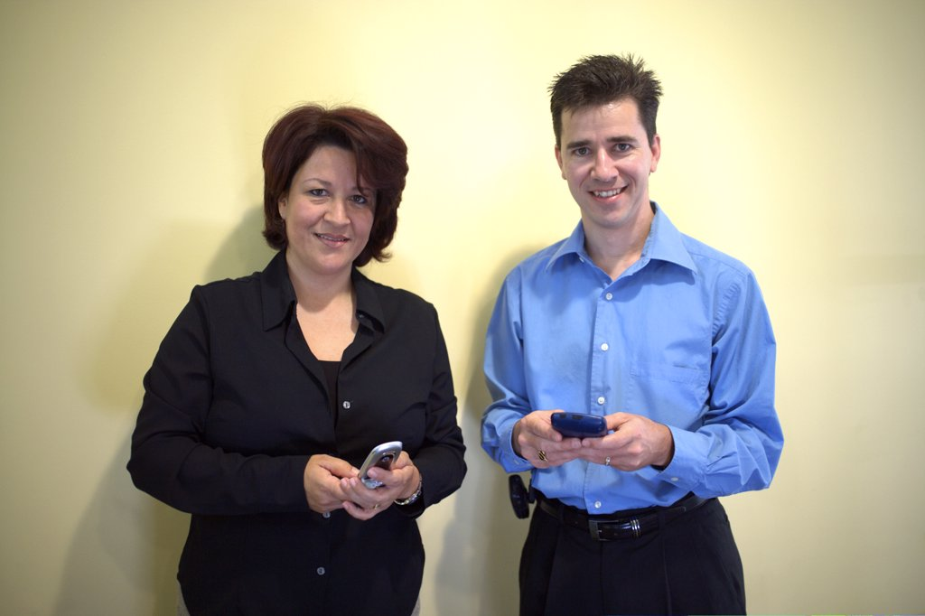 Portrait of a businesswoman and a businessman standing in an office holding a palmtop and a mobile phone : Stock Photo