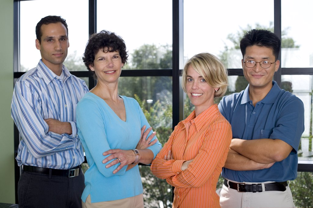 Portrait of a group of business executives standing in an office : Stock Photo