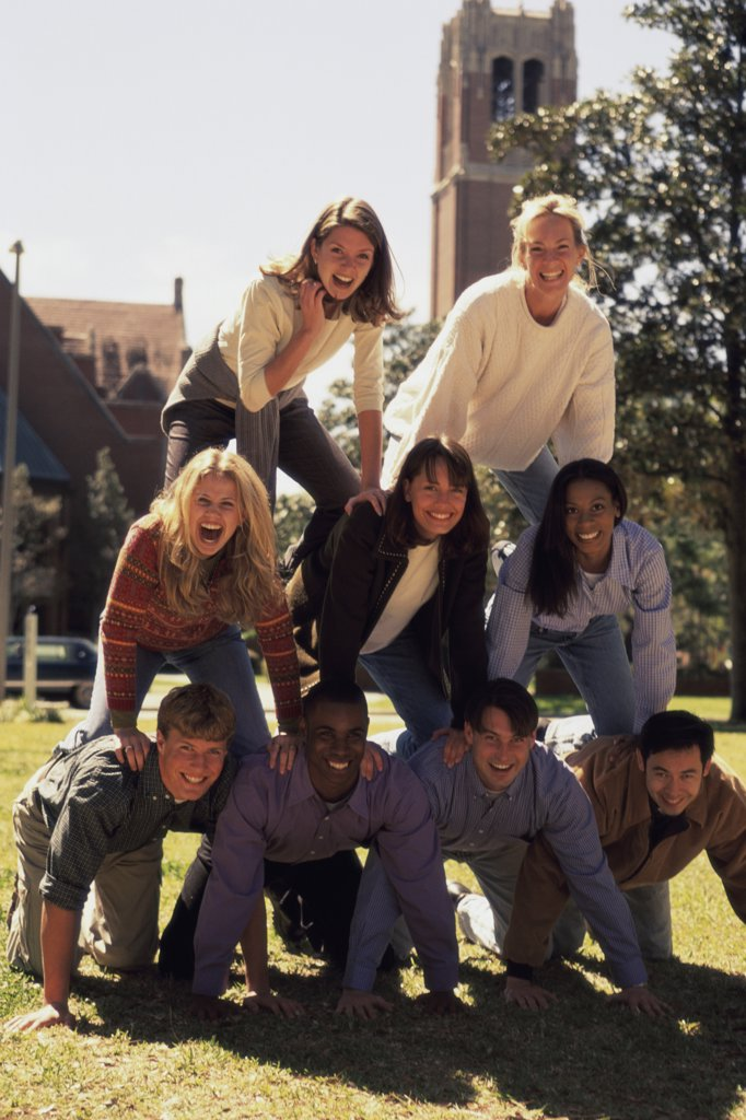 Group of young people making a human pyramid : Stock Photo