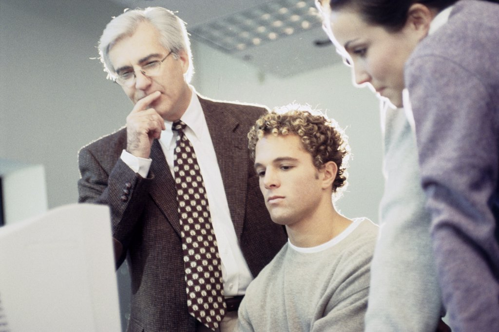 Young man sitting in front of a computer monitor with a professor standing behind him : Stock Photo