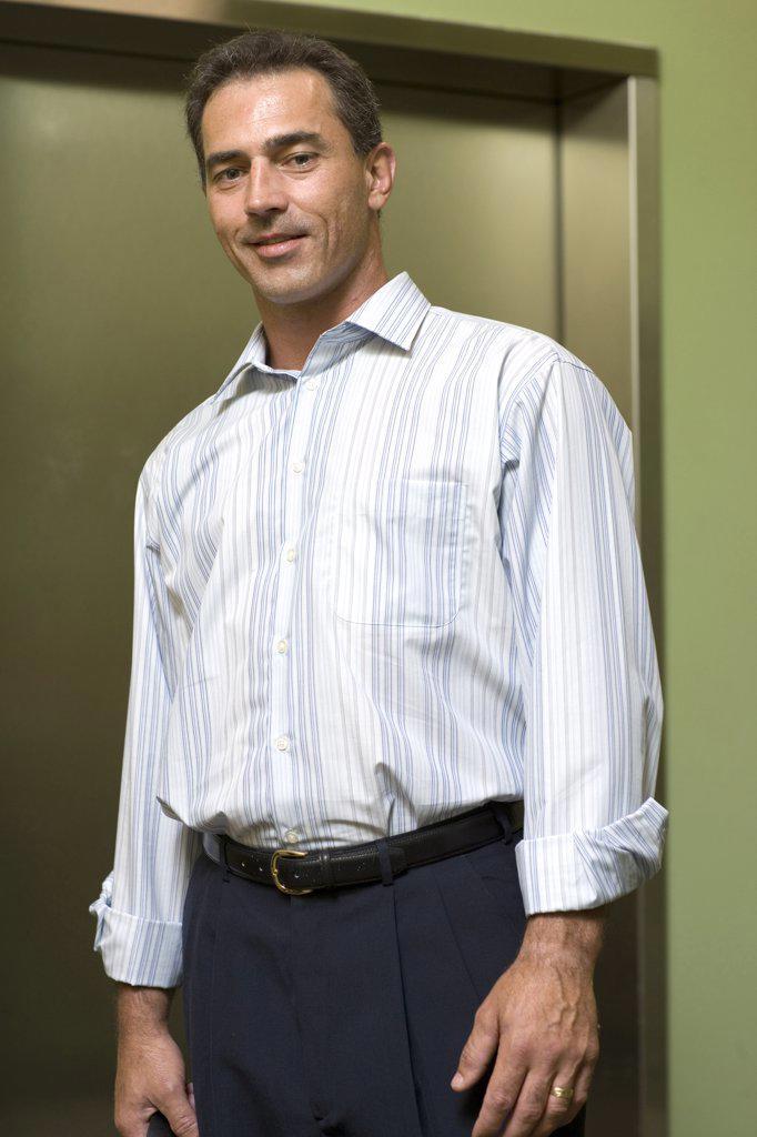 Stock Photo: 1574R-06226 Portrait of a businessman standing near an elevator