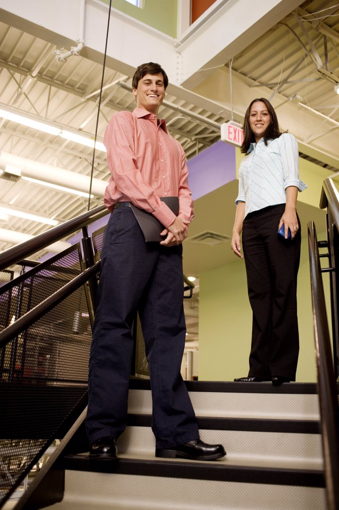 Stock Photo: 1574R-06251 Portrait of a businessman and a businesswoman standing on stairs